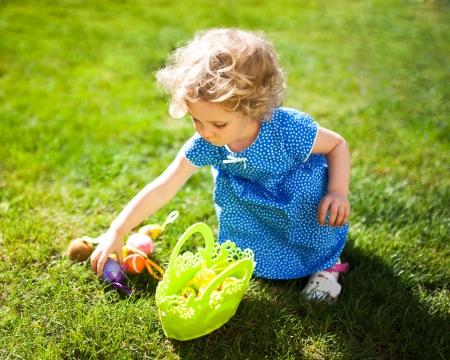 huevos de pascua: Niña en una búsqueda de huevos de Pascua en un prado en primavera Foto de archivo