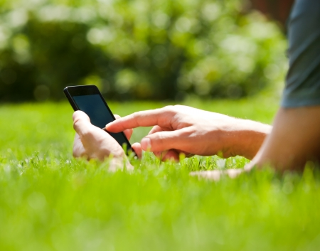 phone professional: Man using mobile smart phone outdoor in summer Stock Photo