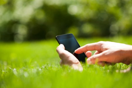 Man using mobile smart phone outdoor in summer Stock Photo