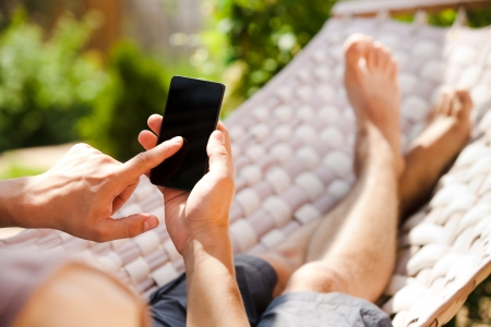 Man using mobile smart phone while relaxing in a hammock