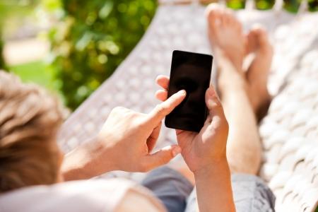 hamaca: Hombre que usa el tel�fono m�vil inteligente mientras se relaja en una hamaca Foto de archivo