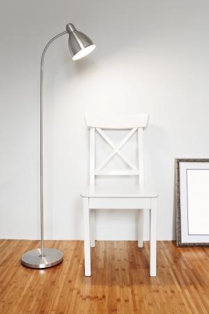 Silla de madera con lámpara de pie para hacer frente a una pared blanca