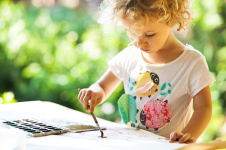 play ground: Portrait of little girl painting, summer outdoor Stock Photo