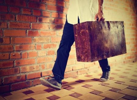 Junger Mann zu Fu� entlang der Stra�e mit alten Koffer, retro get�nten Lizenzfreie Bilder