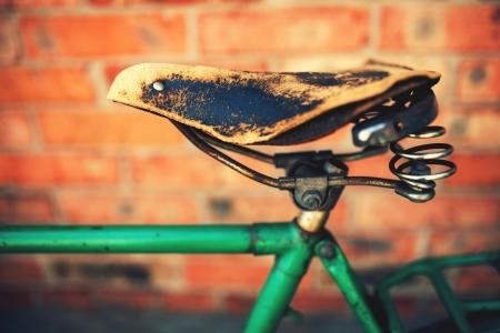 Vintage leather bike saddle with metal spring  photo
