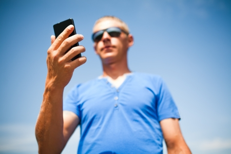 Young man using mobile smart phone, summer outdoor  photo