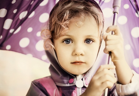 couple in rain: Little cute girl holding an umbrella, close up portrait Stock Photo