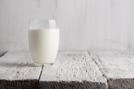 milk jugs: Glass of milk standing on old wooden table