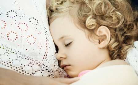 warm home: Mother and daughter sleeping on sofa at home, close up photo