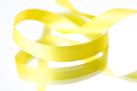 Yellow ribbons isolated on white photo