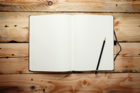 old pencil: Open blank notepad with empty white pages  laying on a wooden table