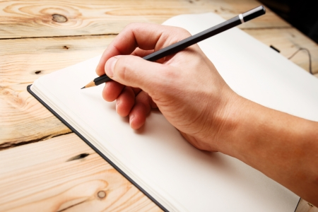 writing letter: In Search Of Inspiration. A man with an empty notebook.  Stock Photo