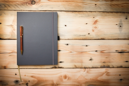 Leather cover note book on wooden  photo