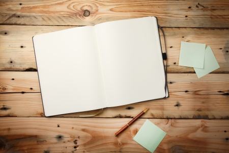 Open blank notepad with empty white pages  laying on a wooden table photo