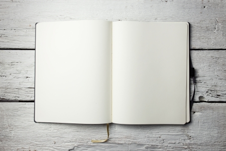 Open blank notepad with empty white pages laying on a wooden table