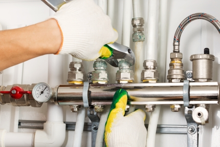 outils plomberie: mains de travailleurs de fixation syst�me de chauffage Banque d'images