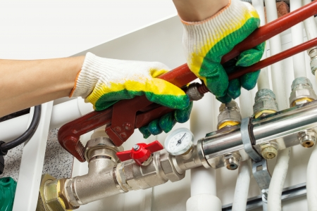 Worker hands fixing heating system photo