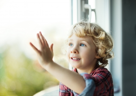 Adorable blond toddler girl looking out of the window photo