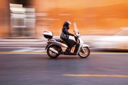motorrad frau: Rollerfahrer mit Bewegungsunschärfe in Rom Italien