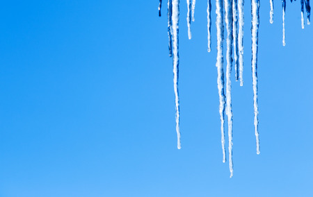 Beautiful icicles glint in the sun against the blue sky  photo
