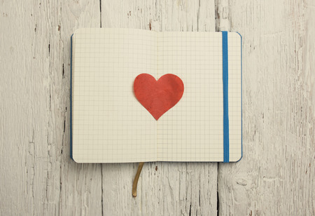 Blank notepad with red heart on wood table  photo