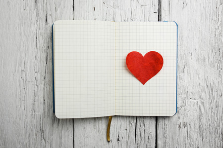 Blank notepad with red heart on wooden table  photo