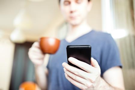 hombre tomando cafe: Hombre de beber caf� y el uso de tel�fonos inteligentes m�viles