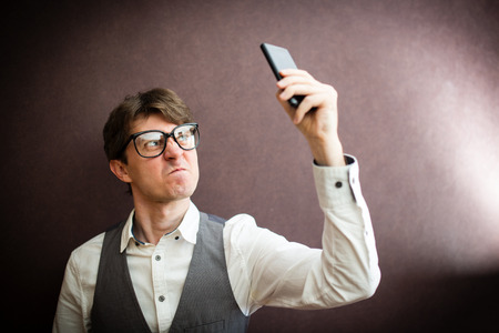 mistrust: Angry man with mobile smartphone Stock Photo