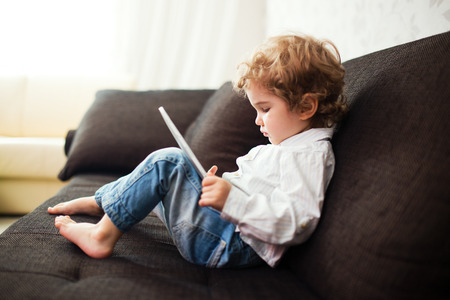 Little boy watching a movie on tablet, indoor