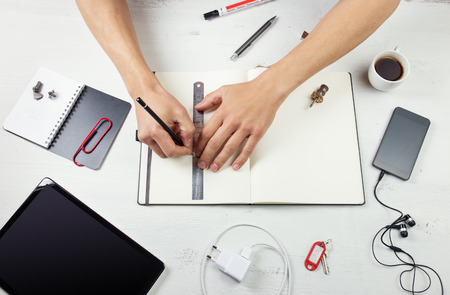 Workplace. Man working on notepad, tablet pc and smart phone on white wooden table photo