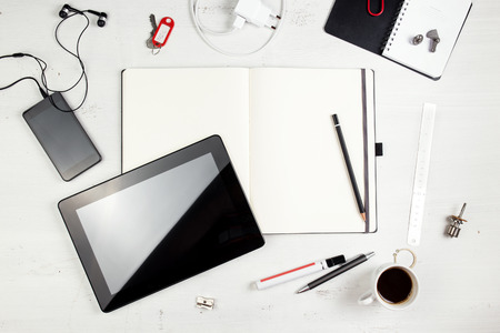 Workplace. Empty notepad, tablet pc and smart phone on white wooden table  photo