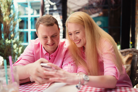Cheerful couple surfing the web, looking a photo on smartphone, summer outdoor cafe  photo