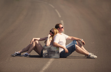 Couple sitting on the road in summer evening, travel concept photo