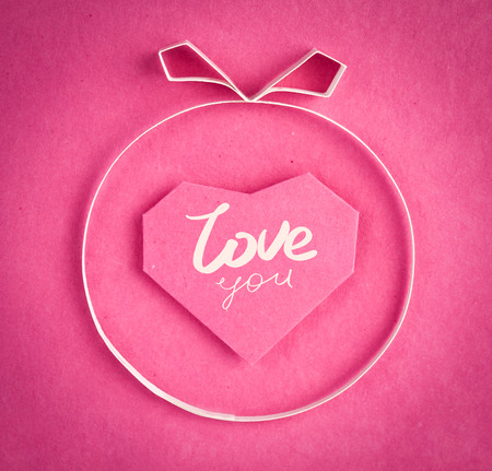 made by hand: Hand made paper heart on pink kraft paper as background. Greeting card