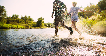 Happy couple running in shallow water. Summertime.