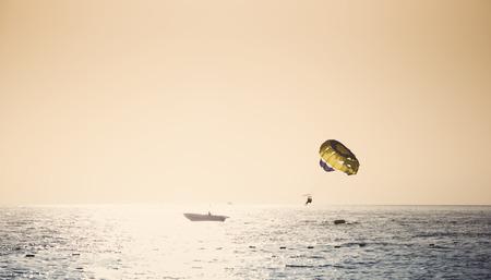 parasailing: Parasailing on parachute over water at sunset