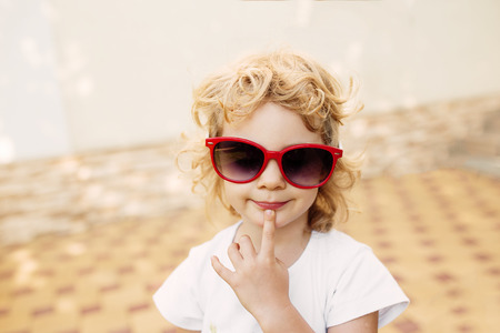 Little girl in red sunglasses, portrait photo