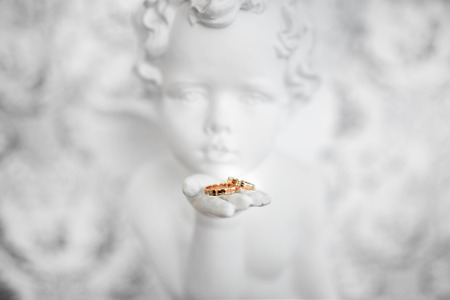 engraver: Two wedding rings in angel hand, close up photo