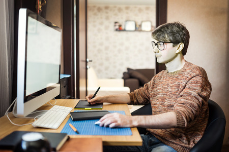 designer chair: Young man at home using a computer, freelance developer or designer working at home.
