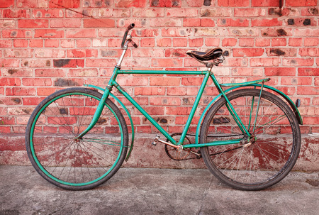 Old retro bicycle against brick wall photo