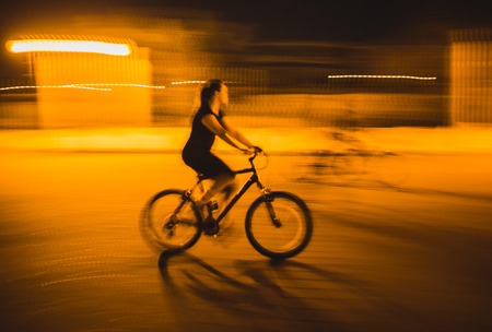 Happy bicyclists riding bikes in a city after sunset, motion blur Stock Photo