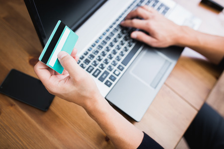 tarjeta de credito: Hombre que sostiene una tarjeta de cr�dito y escribir. On-line de compras en Internet con un ordenador port�til