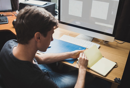 developer: Young man at home using a computer, freelance developer or designer working at home Stock Photo