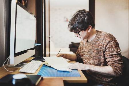 freelance: Young man at home using a computer, freelance developer or designer working at home Stock Photo