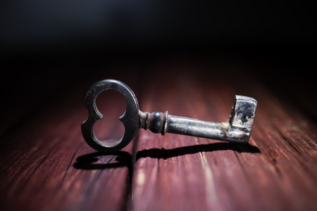 old key: Rusty key on old wooden surface Stock Photo