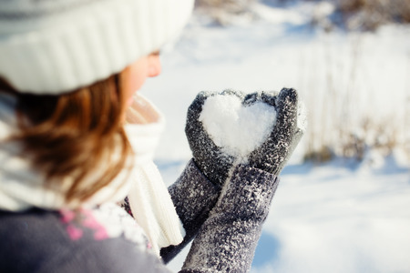 heart shape with hands: Young women holding heart shaped snow in hands Stock Photo