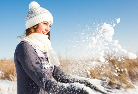 fun in the sun: Happy young woman have fun and enjoy fresh snow at beautiful winter day Stock Photo