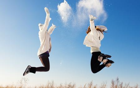 2 つのガール フレンドは楽しいし、美しい冬の日に新雪をお楽しみください。 写真素材
