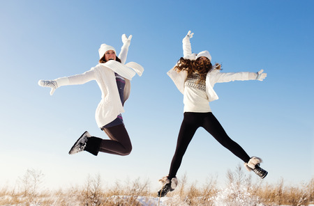 Two girlfriends have fun and enjoy fresh snow at beautiful winter day
