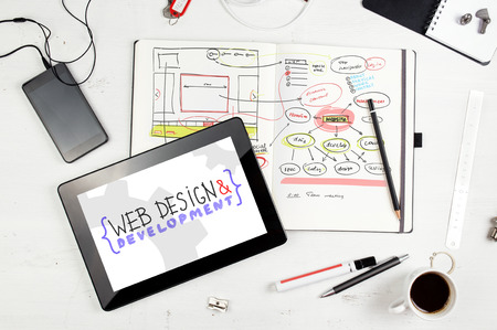 network design: Developer workplace. Open notepad with hand drawn website project. Tablet PC from above Stock Photo